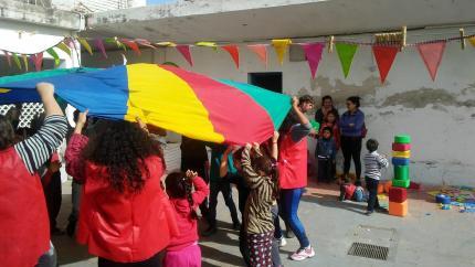 Niñas y niños jugando con tela multicolor.